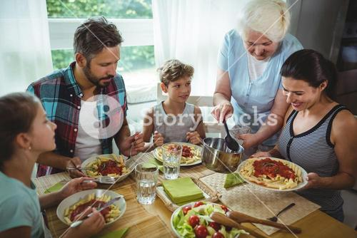 Elderly woman  serving meal to her family