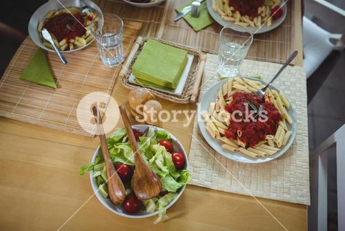 Plates of salad and pasta on dinning table