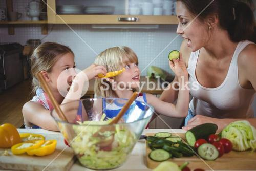 Kids feeding a slice of zucchini to mother in kitchen