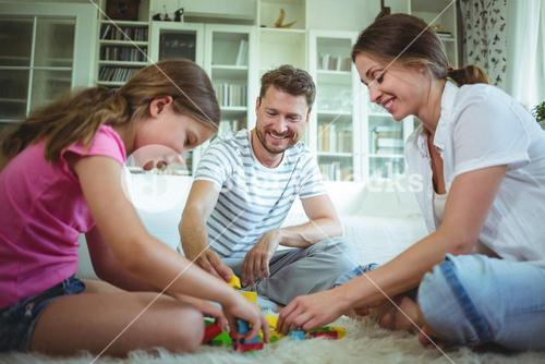 Parents and daughter playing with building blocks