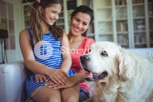 Mother and daughter sitting with pet dog in living room