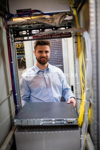Technician removing server from rack mounted server
