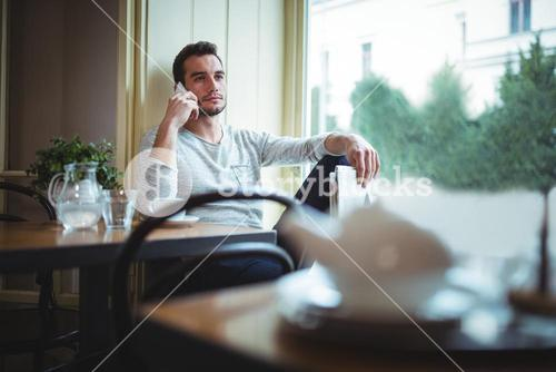 Man sitting at table and talking on mobile phone