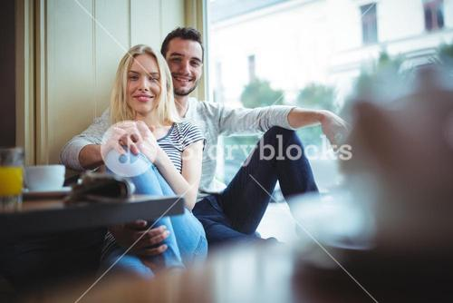 Portrait of smiling couple sitting with arms around