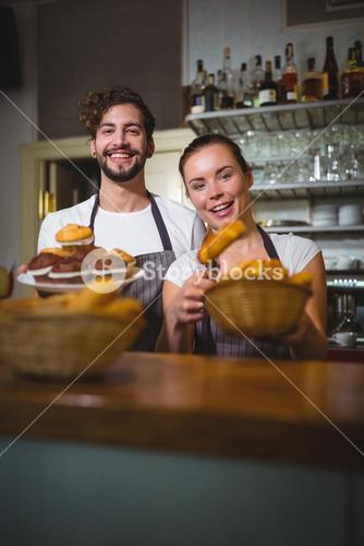 Portrait of waiter and waitress holding cupcakes and bread