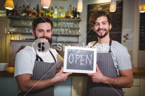 Smiling waiter standing with open sign board in cafe
