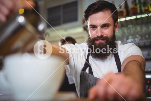 Smiling waiter making cup of coffee at counter
