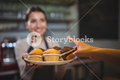 Waitress serving a plate of cupcake to customer