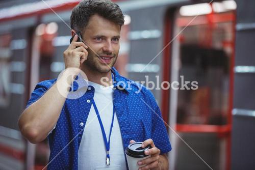Handsome holding disposable cup while talking on mobile phone