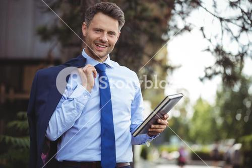 Handsome businessman holding dairy and blazer