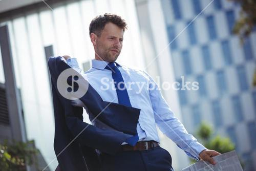 Businessman holding blazer and newspaper