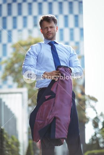 Portrait of handsome businessman holding blazer