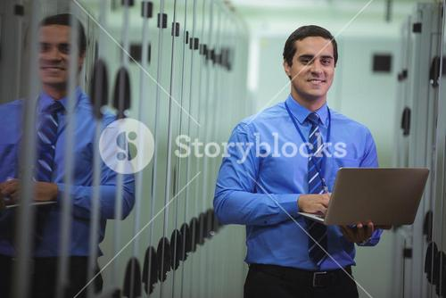 Portrait of technician using laptop while analyzing server