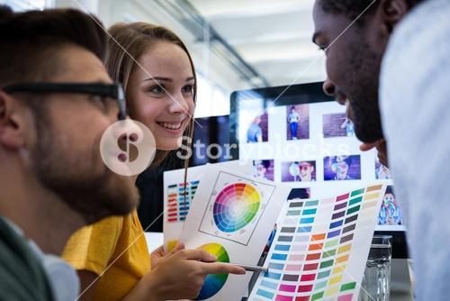 Group of graphic designers choosing color from a color chart