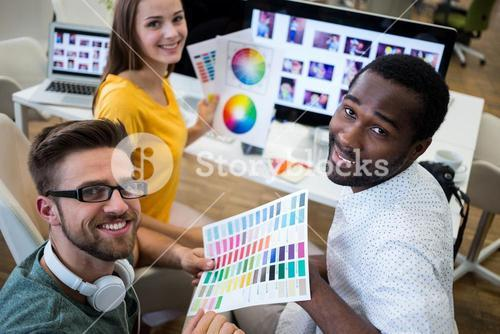 Group of graphic designers holding color chart