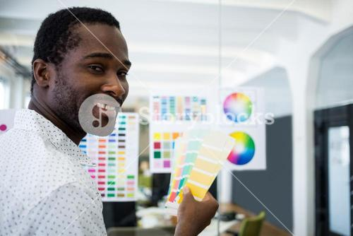 Male graphic designer holding color swatch