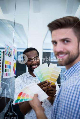 Two male graphic designers holding color swatch