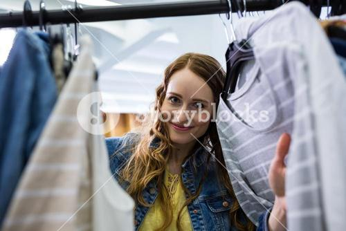 Woman choosing clothes from clothes rack