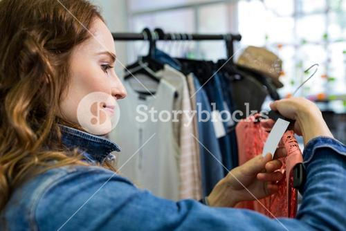 Woman looking at price tag of dress