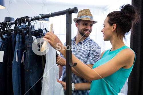 Couple choosing clothes from clothes rack