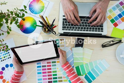 Hands of graphic designers using laptop and digital tablet