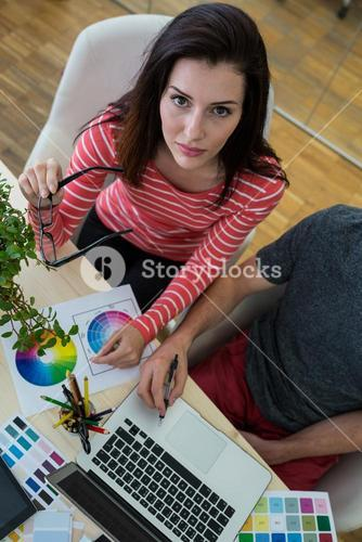Male and female graphic designers using laptop
