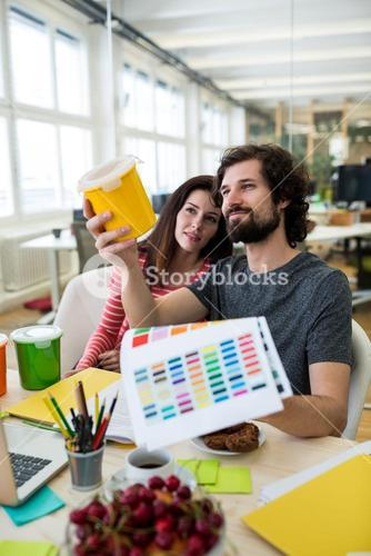 Male and female graphic designers holding plastic container and color chart