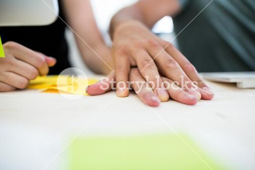 Close-up of couple hands on a desk