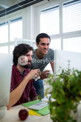 Two male graphic designers holding crumpled paper while working on computer