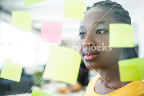 Female graphic designer looking at sticky notes