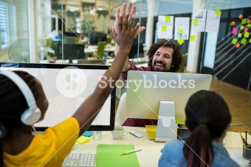 Male graphic designer giving high five to his coworker