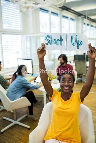 Female business executive holding start up sign