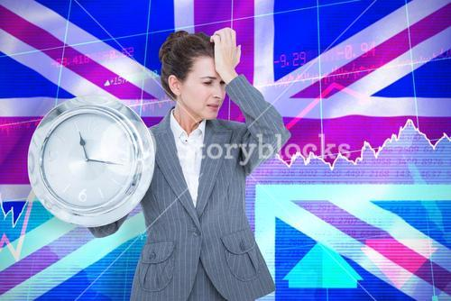 Composite image of upset businesswoman holding wall clock