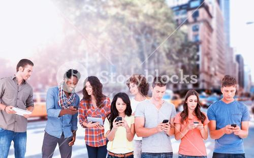 Composite image of four people standing beside each other and texting on their phones