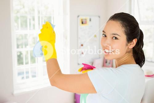 Composite image of smiling woman cleaning walls