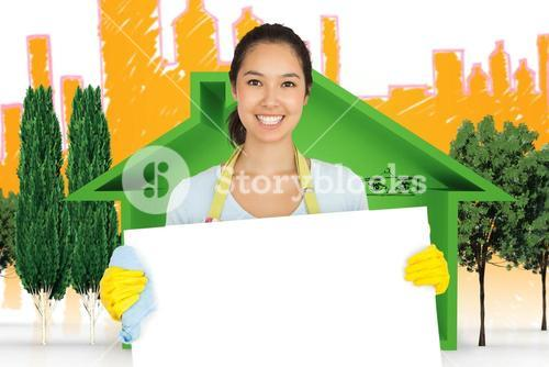 Composite image of woman in apron and rubber gloves holding white surface