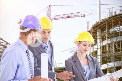 Composite image of businessman explaining a blueprint to his colleagues