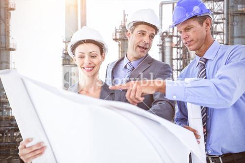 Composite image of businessmen and a woman with hard hats and holding blueprint