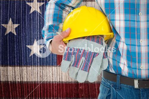 Composite image of construction worker holding hard hat and gloves