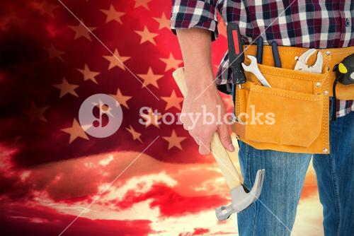 Composite image of repairman wearing tool belt while holding hammer