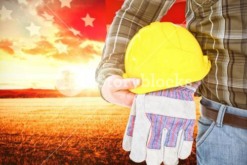 Composite image of manual worker holding helmet and gloves