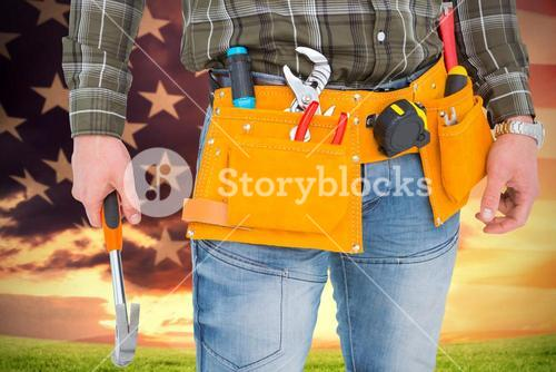 Composite image of manual worker holding hammer