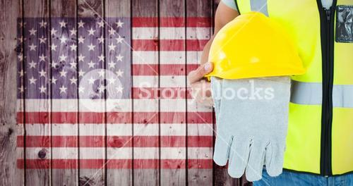 Composite image of construction worker holding gloves and hardhat