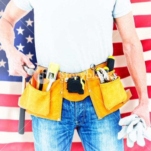 Composite image of technician holding gloves and hammer