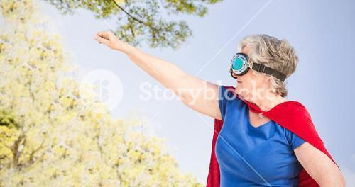 Composite image of senior woman wearing superwoman costume