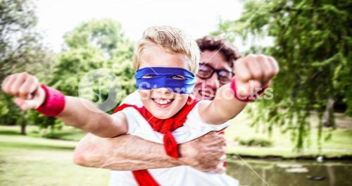 Composite image of father and son dressed as superman