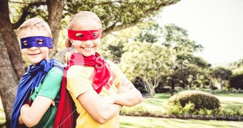Composite image of happy brother and sister in cape and eye mask