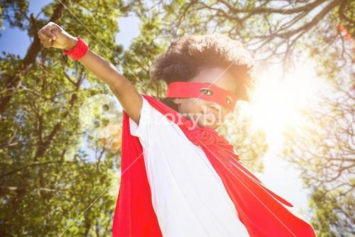 Composite image of portrait of boy in red cape and eye mask
