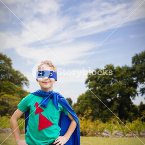 Composite image of portrait of boy in blue eye mask and cape