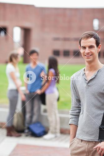 Portrait of a male student posing while his classmates are talking